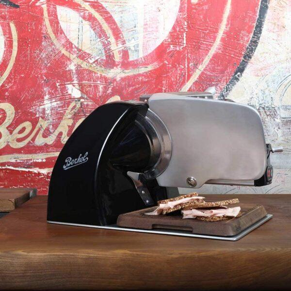 trancheuse noir avec planche à découper sur table en bois