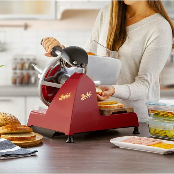 femme qui tranche du pain avec une trancheuse rouge